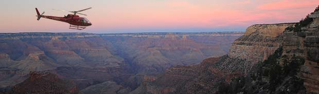 An helicopter flying in the sunset in the Grand Canyon.